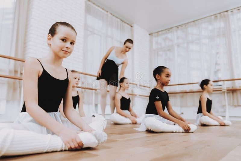 女孩芭蕾训练在地板上的与老师 免版税库存照片