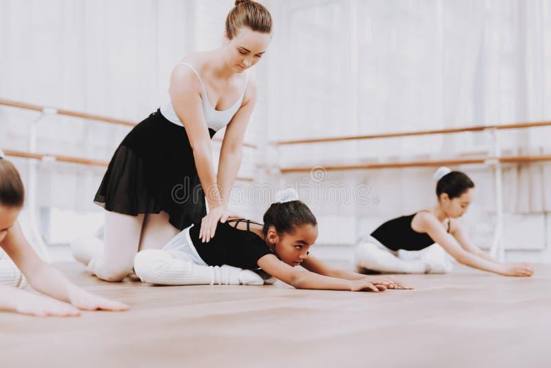 女孩芭蕾训练在地板上的与老师 库存照片