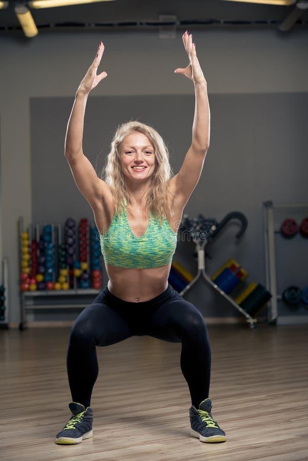 女孩苗条金发碧眼的女人执行蹲坐锻炼 库存图片