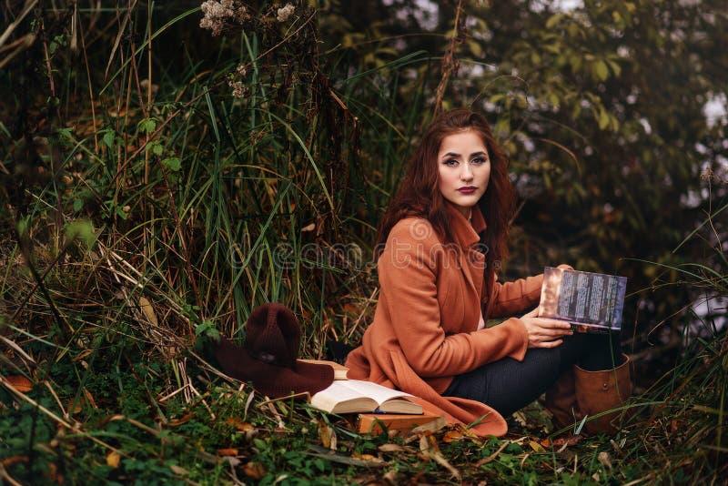 女孩草坪读坐学员课本 图库摄影