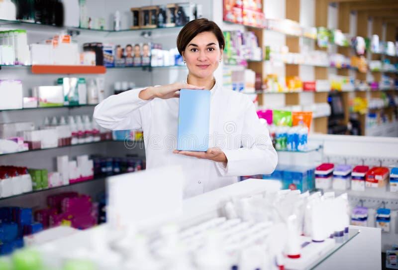 女孩药剂师显示正确的药物 图库摄影