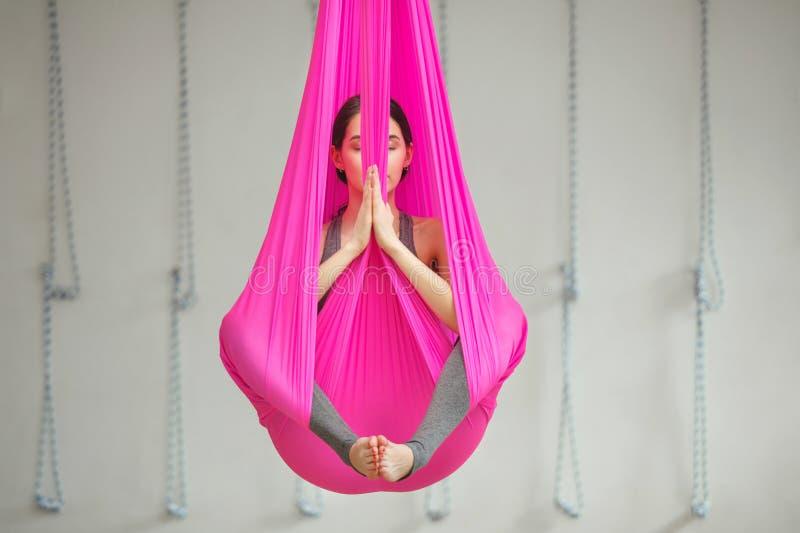 女孩莲花姿势空中反地心引力的瑜伽 妇女在吊床坐 库存图片