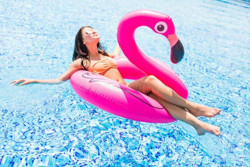 女孩获得乐趣和笑和获得乐趣在一群可膨胀的桃红色火鸟的水池在游泳衣和太阳镜在s 免版税库存图片