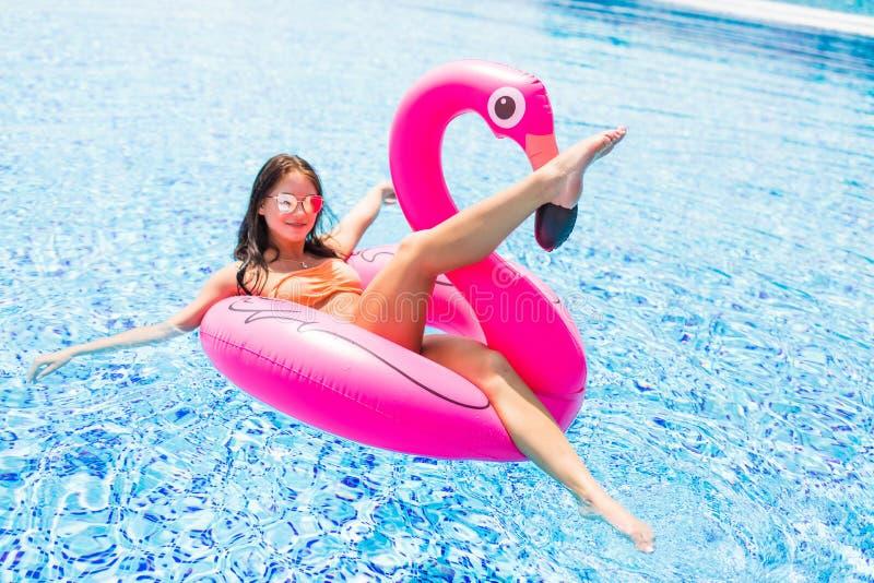 女孩获得乐趣和笑和获得乐趣在一群可膨胀的桃红色火鸟的水池在游泳衣和太阳镜在s 免版税库存照片