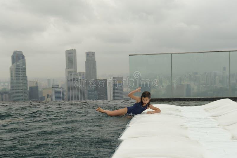 女孩获得乐趣在游泳池 图库摄影