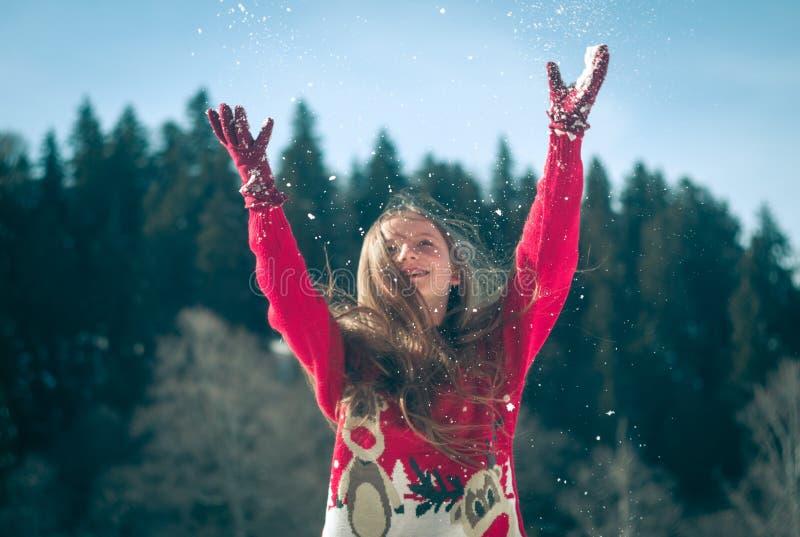 女孩获得乐趣在雪 免版税库存照片