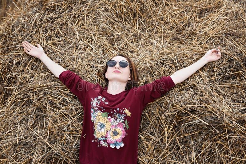 女孩获得乐趣在领域,说谎在干草堆 免版税库存图片