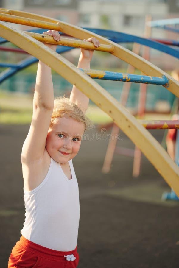 女孩获得在猴子栏杆的乐趣 库存图片