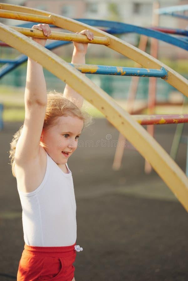 女孩获得在猴子栏杆的乐趣 免版税图库摄影
