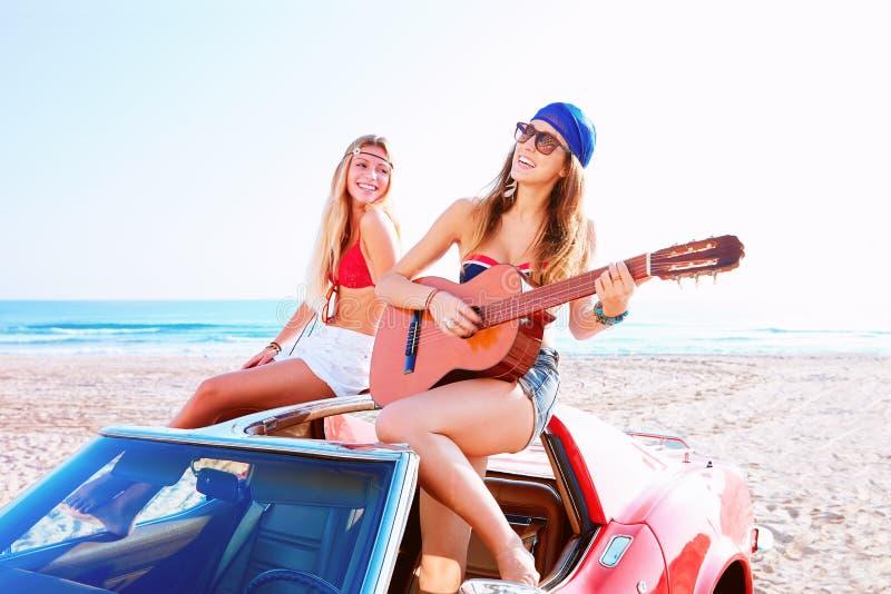 女孩获得弹在Th海滩的乐趣吉他在汽车 免版税库存照片
