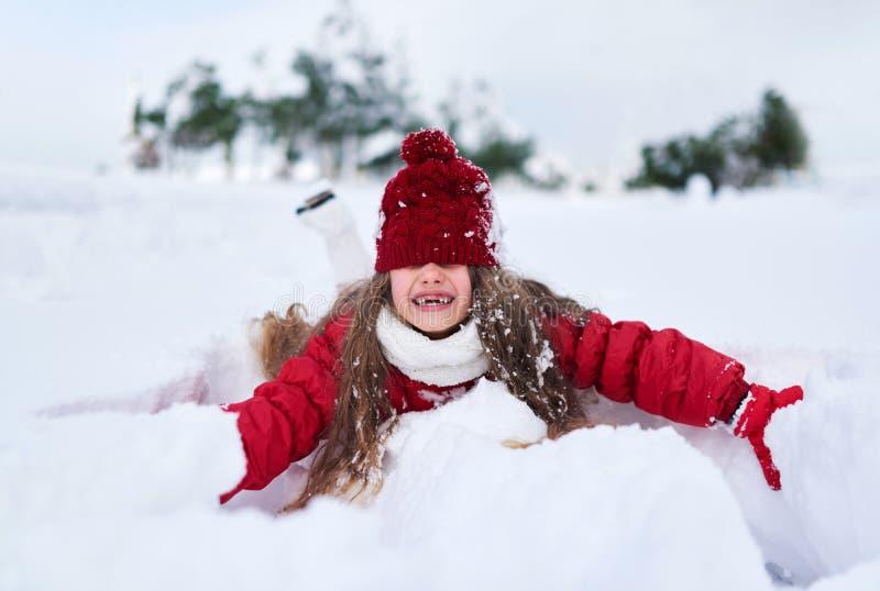 女孩落入雪和笑,帽子覆盖物眼睛 免版税图库摄影
