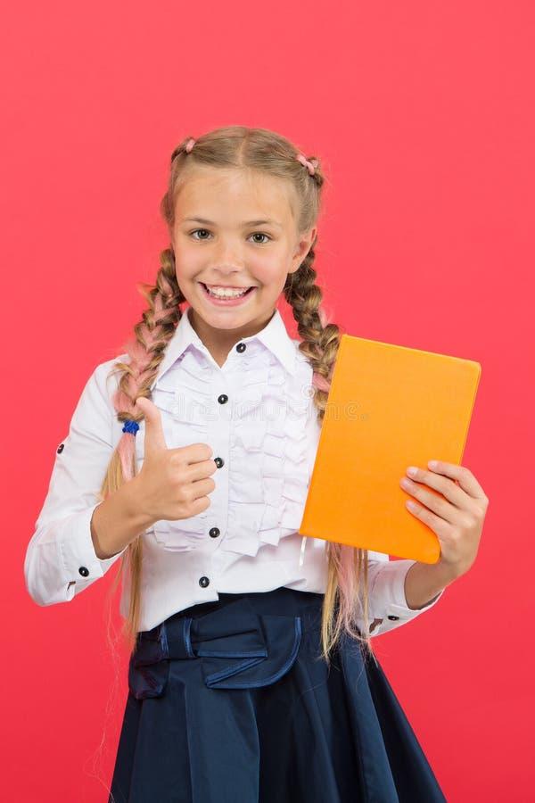 女孩著名为与文具的成见 孩子校服举行书 文具钦佩者 女小学生展示笔记薄 库存图片