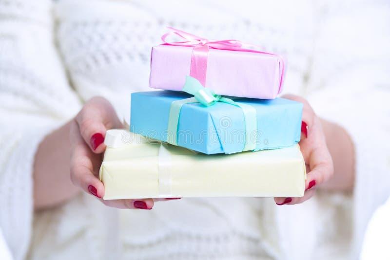 女孩藏品堆礼物盒在手上,有在白色被隔绝的背景的色的装饰纸包裹的礼物的妇女, 免版税库存照片