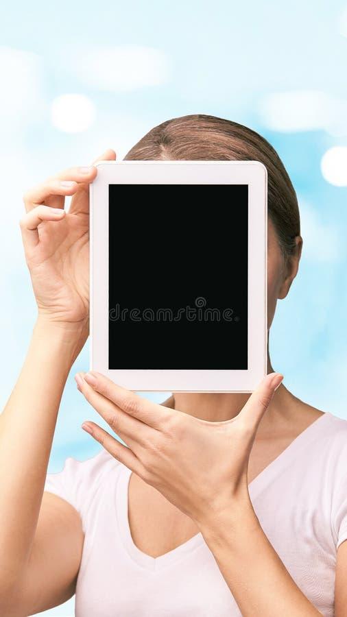 女孩藏品计算机垫 假装在片剂黑色屏幕 在膝上型计算机附近的面孔 妇女陈列个人计算机 免版税库存图片