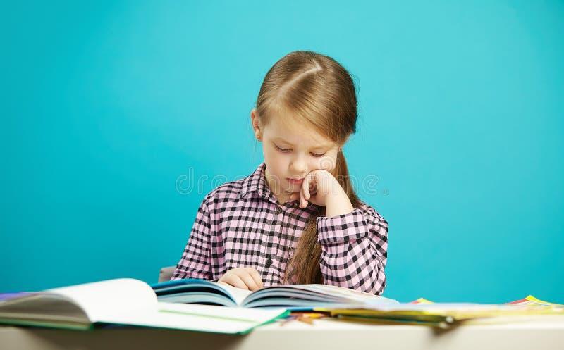女孩被隔绝的画象蓝色背景的,坐在书桌,小心地读书用他的手对下巴 免版税库存照片