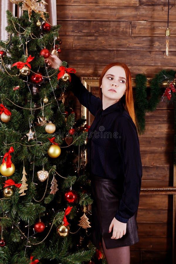 女孩装饰一棵圣诞树 库存照片