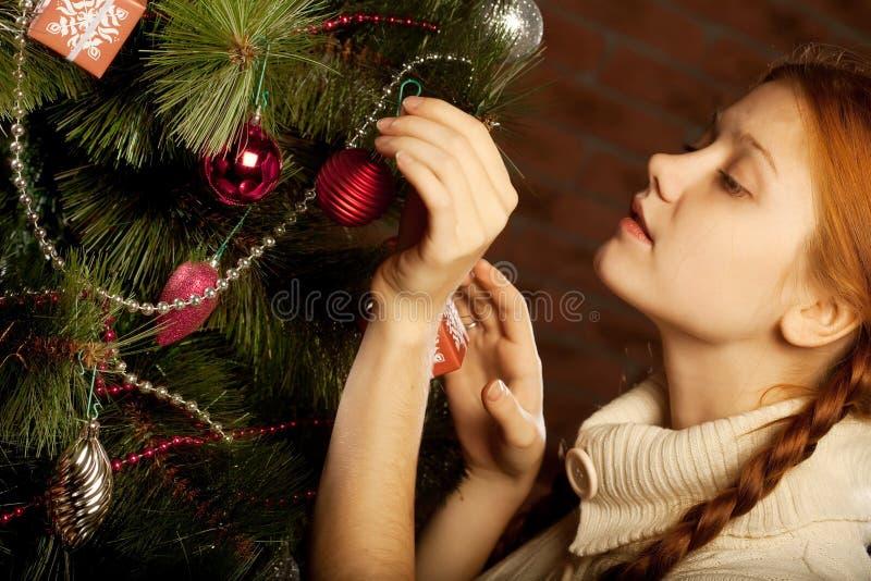 女孩装饰圣诞树 免版税库存图片