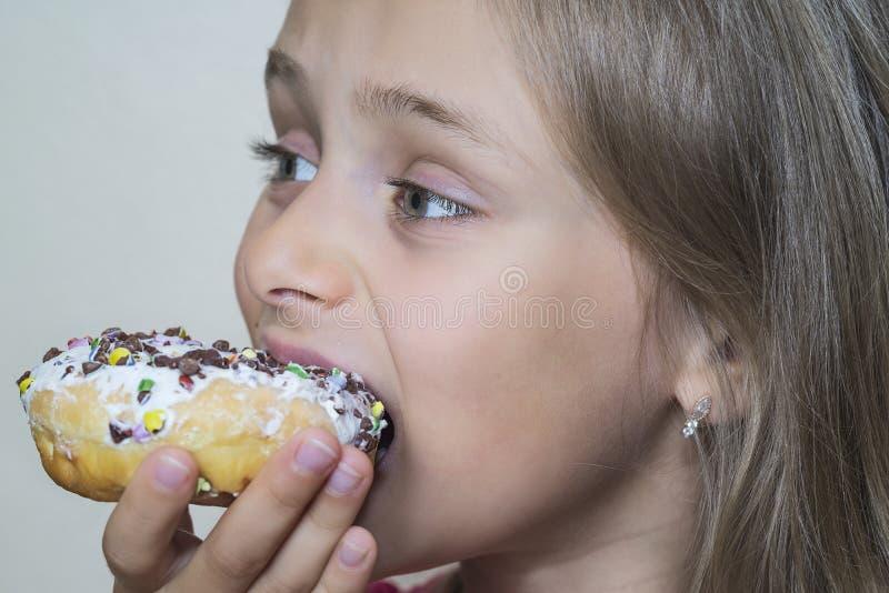女孩要吃甜油炸圈饼 有获得的油炸圈饼的愉快的俏丽的女孩乐趣 快乐的女孩画象有油炸圈饼的 概念饮食 库存照片