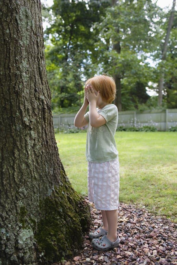 女孩覆盖物眼睛在庭院里 库存图片