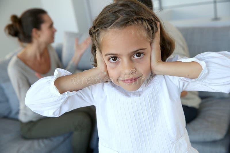 女孩覆盖物耳朵,父母争论 免版税库存图片