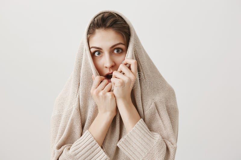 女孩观看单独恐怖电影,打颤从恐惧 可爱的欧洲女性拉扯的毛线衣画象在头的和 免版税图库摄影