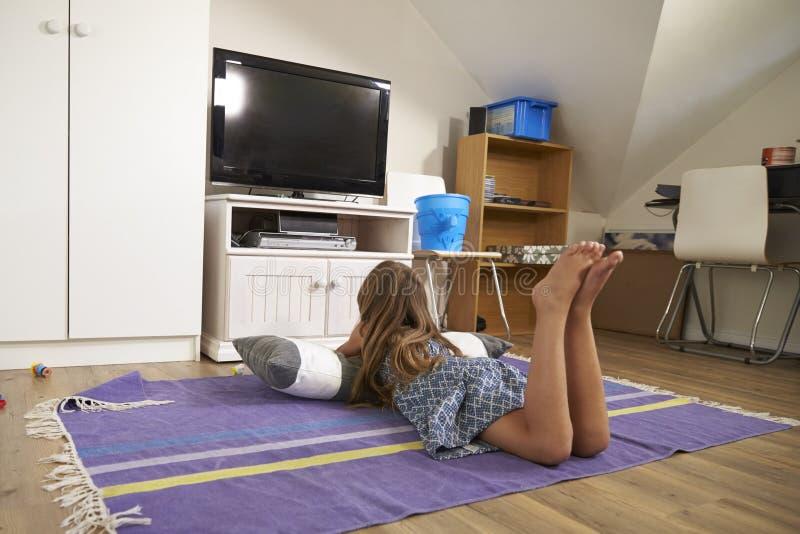 女孩观看的电视背面图在游戏室的 库存照片