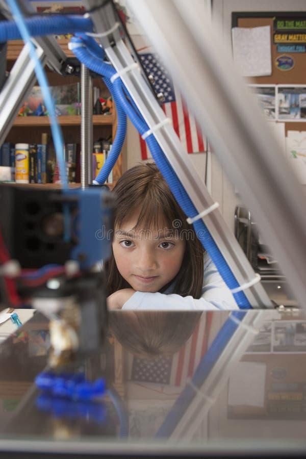 女孩观看3D打印机 免版税库存照片