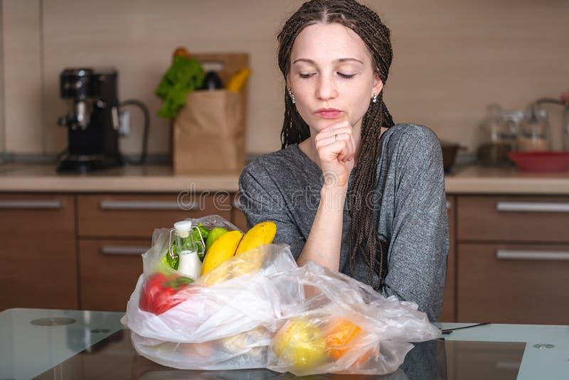 女孩认为那拒绝使用塑料袋买产品 环保和塑料的放弃 免版税图库摄影
