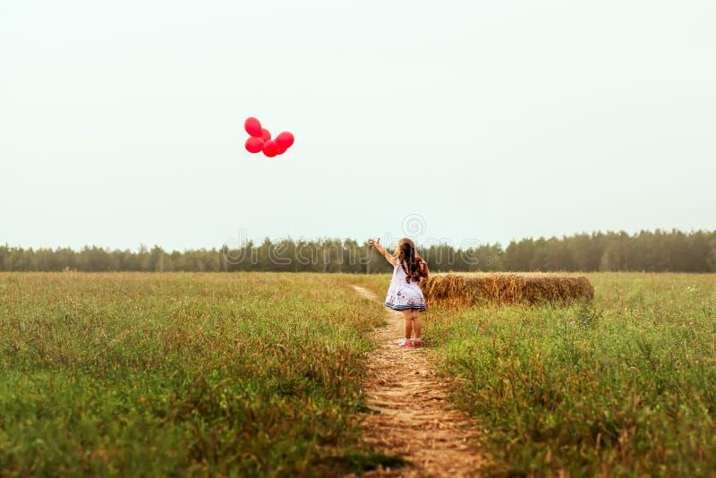 女孩让红色气球飞行到天空 免版税库存照片