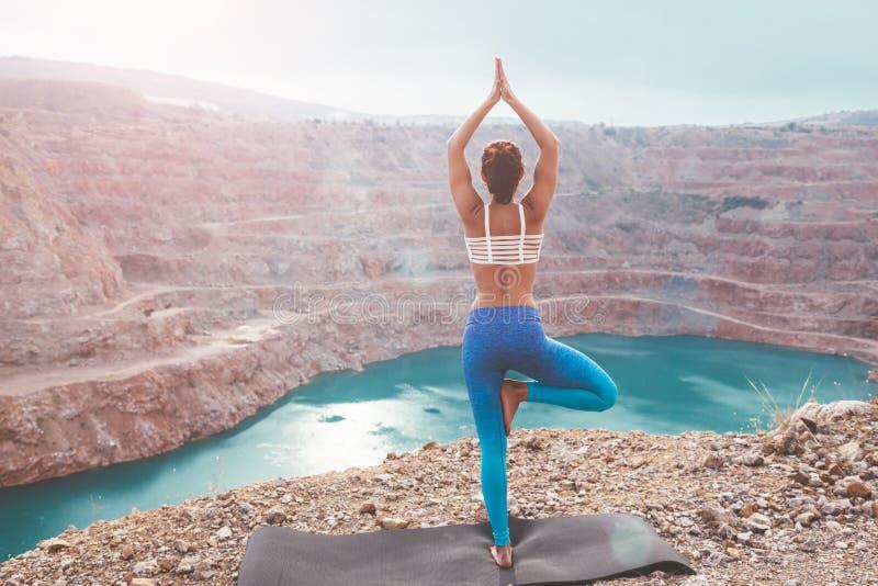 女孩训练室外瑜伽的姿势 免版税库存照片