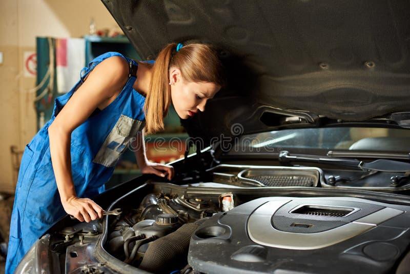 女孩设法修理汽车并且看在它的敞篷下 图库摄影