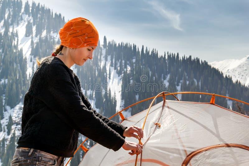 女孩设置旅游帐篷反对积雪的山和蓝天森林的背景与云彩在晴朗的da 免版税库存图片