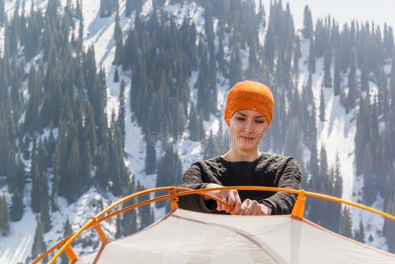 女孩设置旅游帐篷反对积雪的山和蓝天森林的背景与云彩在晴朗的da 免版税库存照片