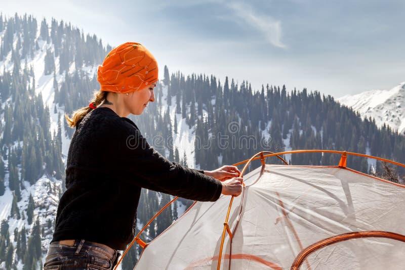 女孩设置旅游帐篷反对积雪的山和蓝天森林的背景与云彩在晴朗的da 库存图片
