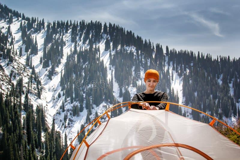 女孩设置旅游帐篷反对积雪的山和蓝天森林的背景与云彩在晴朗的da 图库摄影
