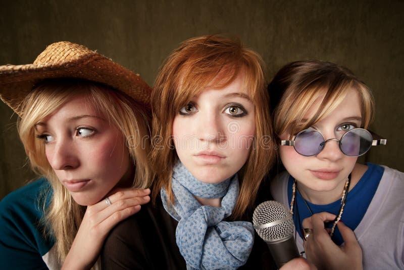 女孩话筒三年轻人 免版税库存图片