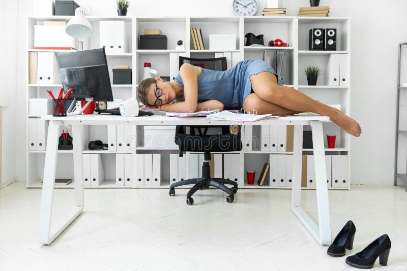 女孩说谎与在文件的闭合的眼睛在书桌上在办公室 免版税图库摄影