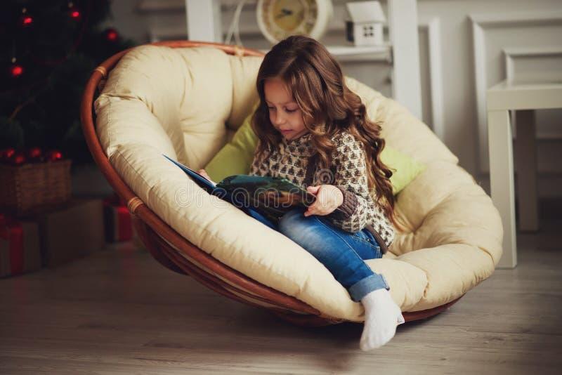 女孩读在家坐的书 免版税库存图片