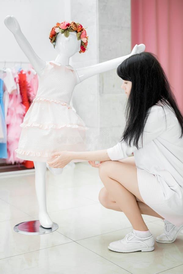 女孩调整在时装模特的礼服 免版税库存图片