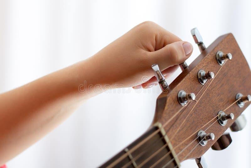 女孩调整声学吉他,特写镜头的` s手照片  图库摄影