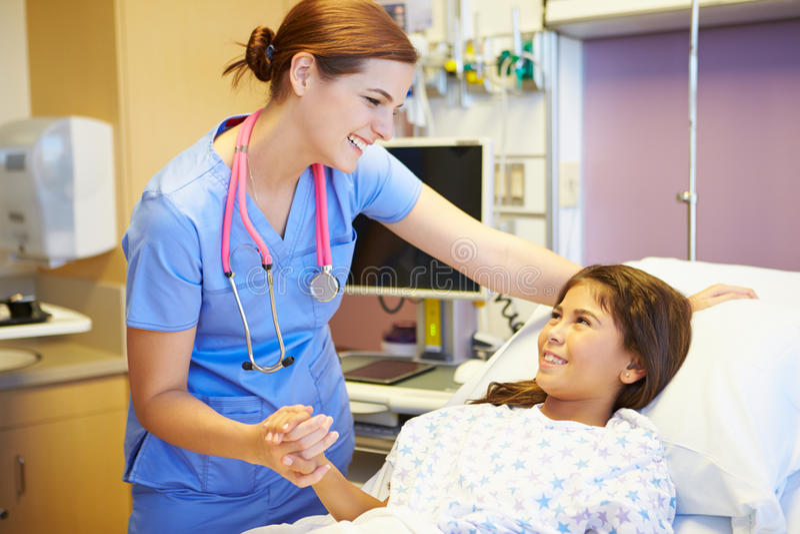 女孩谈话与女性护士在医房 免版税图库摄影