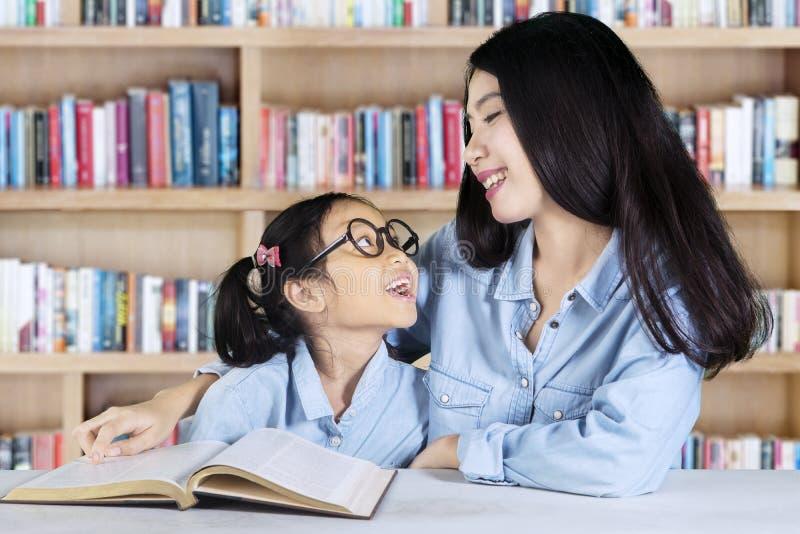 女孩谈话与老师在图书馆里 免版税库存照片
