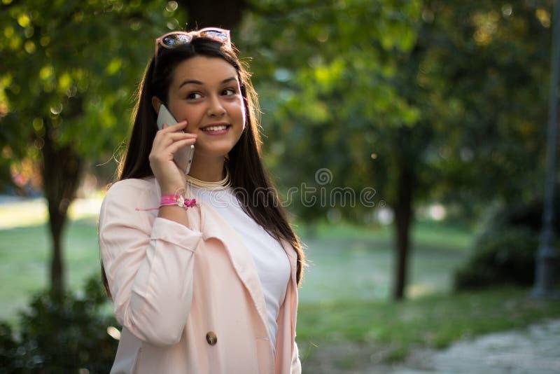 女孩谈话在智能手机户外 库存照片