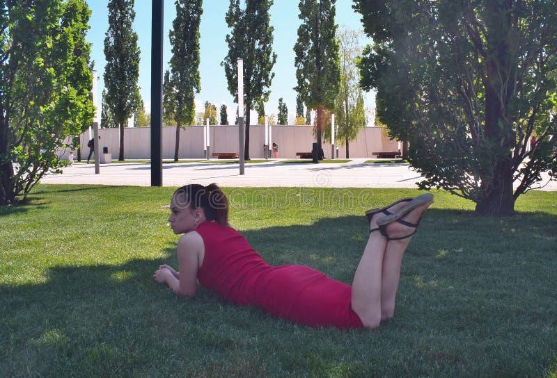 女孩谈话在说谎在绿草的电话在公园在夏天 免版税库存照片
