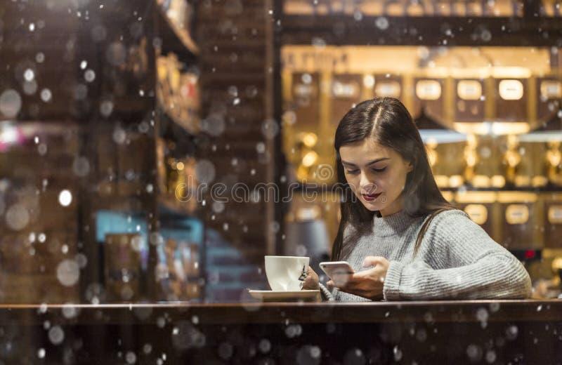 女孩谈话由在咖啡馆的电话 库存照片