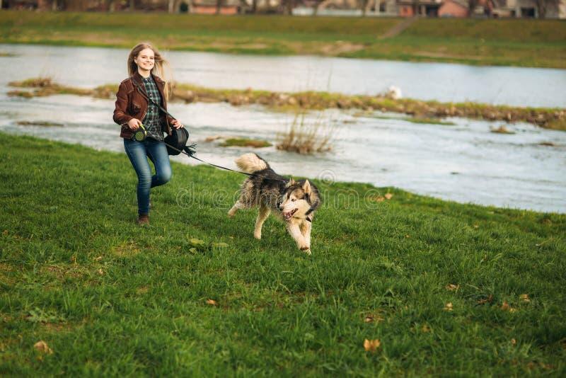 女孩走与沿堤防的一条狗 美丽的多壳的狗 海岸冰横向河水冬天 春天 免版税库存图片