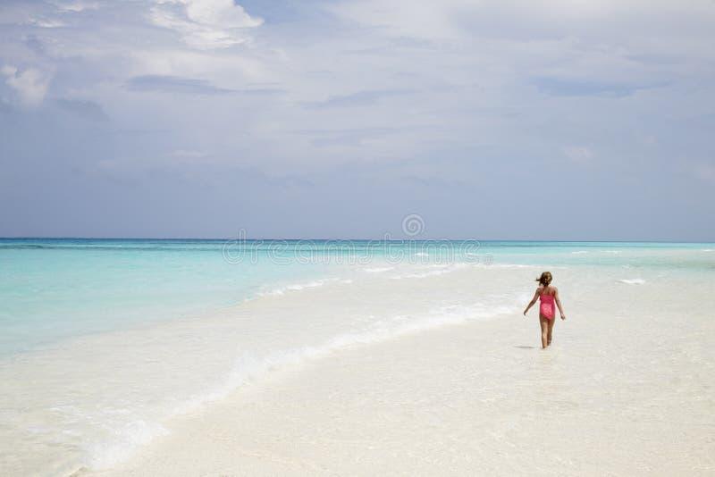 女孩走在一个空的白色沙子海滩的,后面看法 免版税库存照片