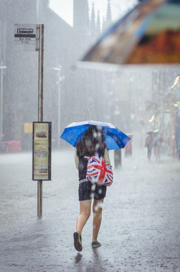 女孩走在夏天雨在城市 免版税库存照片