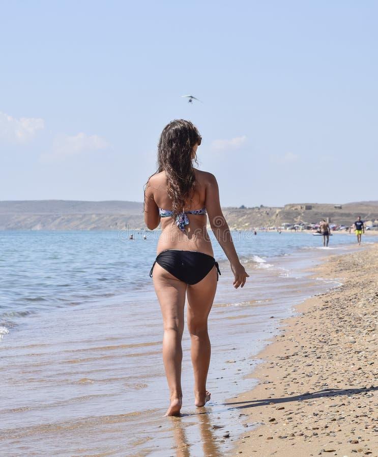 女孩走在海滩的,背面图 免版税库存图片