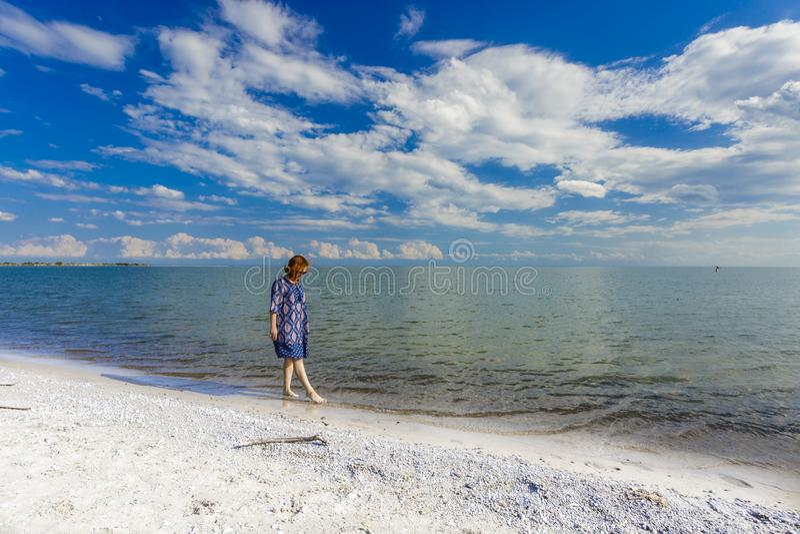 女孩走在湖海滩的蓝色礼服的 免版税库存图片